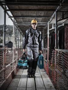 Мужчина в рабочей одежде несет инструменты