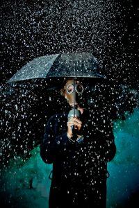 Человек с зонтом под дождем